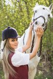 Beautiful brunette girl with long hair posing with a red horse in forest. Autumn landscape, beautiful brunette girl with long hair posing with a red horse in the Royalty Free Stock Photography
