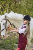 Beautiful brunette girl with long hair posing with a red horse in forest. Autumn landscape, beautiful brunette girl with long hair posing with a red horse in the Royalty Free Stock Photos