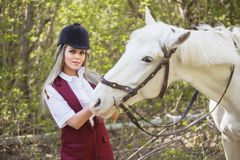 Beautiful brunette girl with long hair posing with a red horse in forest. Autumn landscape, beautiful brunette girl with long hair posing with a red horse in the Stock Images
