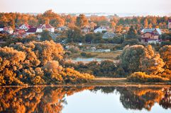 Autumn landscape. Birds eye view of small village in the autumn forest at sunrise. Wooden houses between the yellowed autumn trees near the bank of the river Stock Image