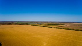 Autumn landscape: blue sky, colorful trees, yellow fields. Aerial view stock photos