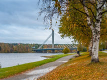 Autumn landscape with bridge. Park alley in autumn colors with bridge over the river in the background, Rovaniemi, Finland Royalty Free Stock Photo