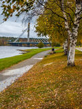Autumn landscape with bridge. Park alley in autumn colors with bridge over the river in the background, Rovaniemi, Finland Royalty Free Stock Images
