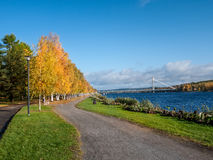Autumn landscape with bridge. Park alley in autumn colors with bridge over the river in the background, Rovaniemi, Finland Stock Image