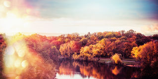 Autumn landscape of  City Park with colorful trees and lake at sunset light with bokeh, panoramic Royalty Free Stock Image