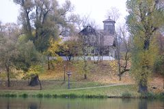 Autumn landscape in the city park. You can see the water surface of the lake, yellowed foliage and footpaths. Stock Photo