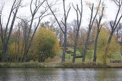 Autumn landscape in the city park. You can see the water surface of the lake, yellowed foliage and footpaths. Royalty Free Stock Photos