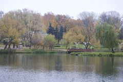 Autumn landscape in the city park. You can see the water surface of the lake, yellowed foliage and footpaths. A wooden bridge conn Royalty Free Stock Image