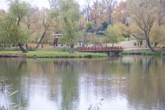 Autumn landscape in the city park. You can see the water surface of the lake, yellowed foliage and footpaths. A wooden bridge conn Stock Images