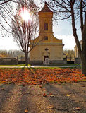 Autumn landscape with colourful leaves and a catholic church in Banat. Afternoon autumn landscape with colorful leaves and a catholic church in Banat, in Opovo Royalty Free Stock Photography