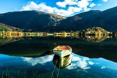 Autumn Landscape com um barco solitário, umas montanhas, umas árvores coloridas e um céu azul refletidos no lago fotos de stock