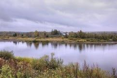 Autumn Landscape De Tura-rivier en een eenzaam oud blokhuis op de tegenovergestelde Bank Royalty-vrije Stock Foto