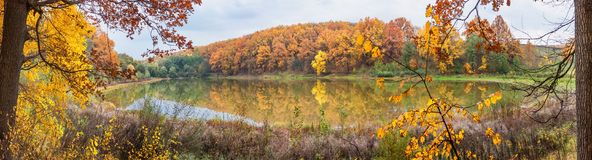 Autumn landscape - the forest by lake in the sunny autumn day. Panorama, banner royalty free stock photography