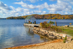 Autumn Landscape with a Gazebo. On a lakeshore, colourful trees, lake, sky and clouds Stock Images