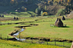 Autumn landscape with haystacks in a valley Royalty Free Stock Images