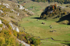 Autumn landscape with haystacks in a valley Stock Photography