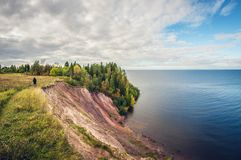Autumn landscape. high cliff on lake. A girl walking on the edge of a cliff. Autumn landscape. high cliff on the lake. A girl walking on the edge of a cliff stock images
