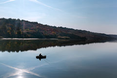 Autumn landscape at the lake. Autumn landscape with fisherman on the pond Royalty Free Stock Photo