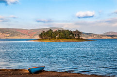 Autumn landscape with lake, island and boat Stock Images