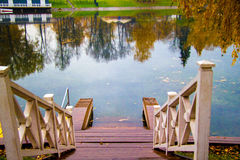 Autumn landscape. Autumn lake surrounded by a yellow wood. trees reflected in the water. Cloudy skyThe staircase leading to the water stock photo
