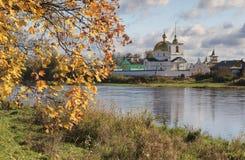 Autumn landscape with maple branch and river. And Spaso-Kazan Simansky monastery Ostrov, Pskov oblast stock photography
