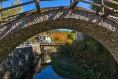 Autumn Landscape med Roman Bridge och kyrkan av antagandet i stad av Shiroka Laka, Bulgarien royaltyfria bilder