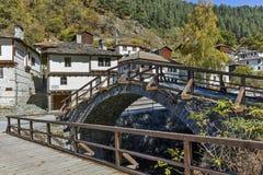 Autumn Landscape med Roman Bridge och kyrkan av antagandet i stad av Shiroka Laka, Bulgarien royaltyfria foton
