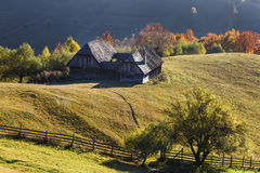 Autumn Landscape mit einem Holzhaus auf den Steigungen der Berge Schöne Licht- und Sonnenstrahlen Lizenzfreies Stockfoto