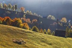 Autumn Landscape mit einem Holzhaus auf den Steigungen der Berge Schöne Licht- und Sonnenstrahlen Stockfoto