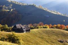 Autumn Landscape mit einem Holzhaus auf den Steigungen der Berge Schöne Licht- und Sonnenstrahlen Lizenzfreie Stockbilder