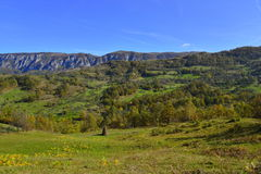 Autumn landscape with mountain village, haystack and mountains at distance in Romania Stock Images
