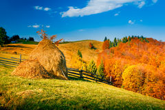 Autumn landscape in a mountain village. Two stack of dry hay. Beautiful evening clouds. Carpathian mountains, Ukraine, Europe Stock Photography