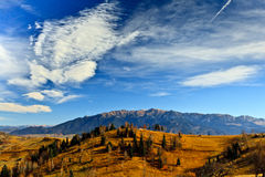 Autumn landscape with mountains and blue sky. View of Bucegi mountains (Romania) in autumn at sunset Stock Photos