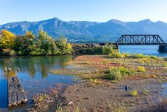 Railway bridge over a marshy strait on the Columbia River. Autumn landscape with an old abandoned rotten wooden pier in the bay of the Columbia River with yellow royalty free stock photography