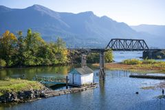 Old pier in the Columbia River Plant separated by railway bridge. Autumn landscape with an old abandoned rotten wooden pier in the bay of the Columbia River with royalty free stock photography