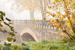 Autumn Landscape with an old stone bridge Stock Photos