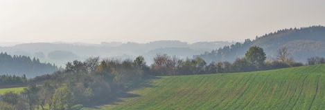 Autumn landscape. The panorama of autumn forests covered in the fog. Green field bordered by the trees is in the foreground. The sun makes tree shadows on the stock photo