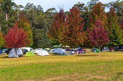 Autumn landscape with people camping in the distance. Autumn landscape with unrecognisable people camping with tents in the distance Stock Image