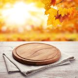 Autumn landscape and pizza board with napkin on wooden table. Top view mock up stock photo