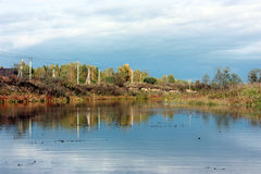 Autumn landscape. The river in which is reflected sky and clouds Stock Images