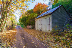 Autumn landscape with road and a barn Royalty Free Stock Photos