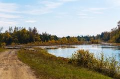 Autumn landscape. The road runs along the river. Royalty Free Stock Photos