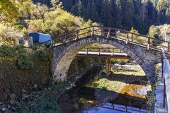 Autumn Landscape with Roman Bridge and old houses in town of Shiroka Laka, Bulgaria Royalty Free Stock Photo
