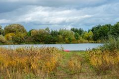 Autumn landscape. The shore of a small lake in sunny autumn day Stock Images