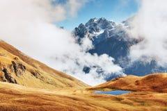 Autumn landscape and snow mountains in beautiful cumulus clouds. Main Caucasian Ridge. Type Mount Ushba Mheyer, Georgia Royalty Free Stock Photos