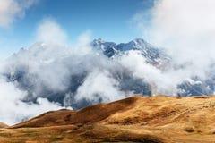 Autumn landscape and snow mountains in beautiful cumulus clouds. Main Caucasian Ridge. Type Mount Ushba Mheyer, Georgia.  royalty free stock photography