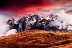Autumn landscape and snow mountains in beautiful cumulus clouds. Main Caucasian Ridge. Type Mount Ushba Mheyer, Georgia Royalty Free Stock Photography