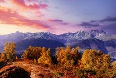 Autumn landscape and snow mountains in beautiful cumulus clouds. Main Caucasian Ridge. Type Mount Ushba Mheyer, Georgia Stock Photos