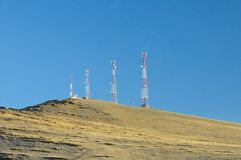 Autumn landscape with a telecommunication towers on top of a hill covered with dry yellow grass stock image