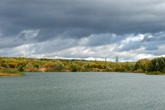 Thunder Sky. Autumn landscape. Autumn trees at the bank of the river in sunny autumn day Royalty Free Stock Photography